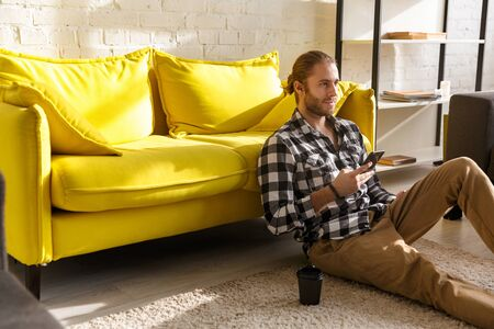 Photo of young handsome man wearing plaid shirt holding cellphone and sitting on floor in apartment