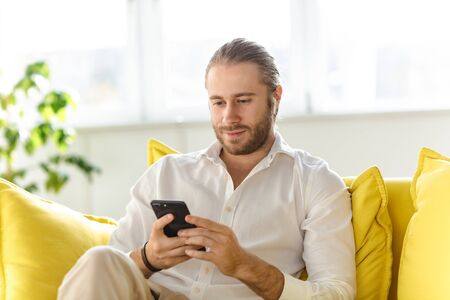 Photo of young handsome businessman wearing white shirt holding cellphone while sitting on sofa in apartment