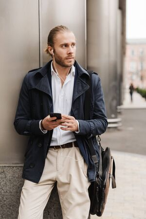 Attractive young blonde haired man in formal wear talking through earphones, holding mobile phone while standing outdoors on a city street