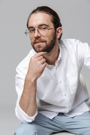 Image of a young serious concentrated handsome bearded man in glasses posing isolated over grey wall background.