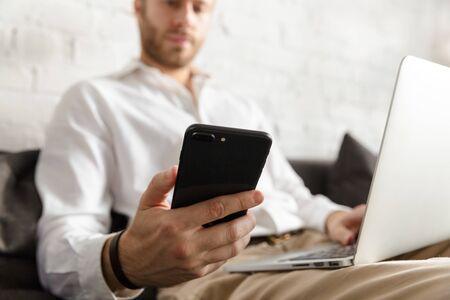 Photo of young handsome businessman holding cellphone and using laptop computer in apartment
