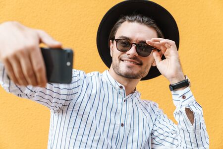 Image of young joyful man wearing sunglasses and black hat smiling and taking selfie at cellphone isolated over yellow background