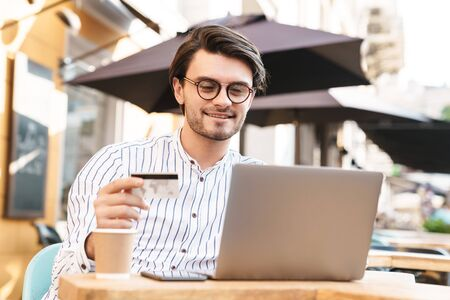 Photo of smiling young man wearing eyeglasses using laptop and holding credit card while drinking coffee in cafe outdoors