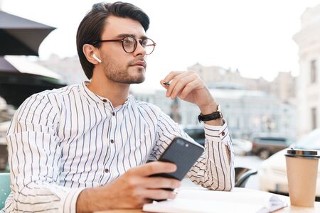 Photo of thinking caucasian man wearing eyeglasses using earpod and cellphone while working in cafe outdoors