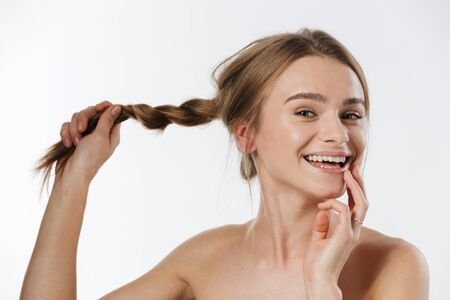 Beauty portrait of gorgeous young blonde half-naked woman smiling and holding her braid isolated over white background Stock fotó