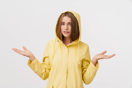 Photo of unhappy young woman in raincoat posing and looking at camera isolated over white background