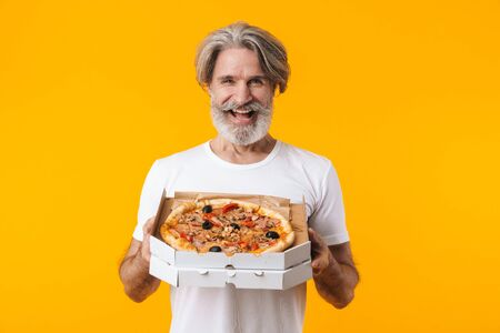 Image of positive smiling senior grey-haired bearded man posing isolated over yellow wall background eat pizza.
