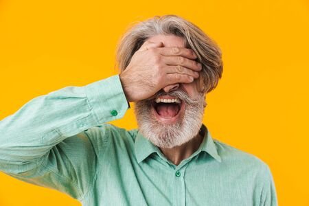 Picture of screaming elderly grey-haired bearded man in blue shirt posing isolated over yellow wall background covering eyes.