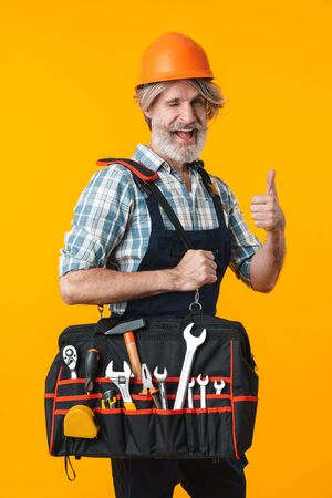 Photo of positive elderly grey-haired bearded man builder in helmet posing isolated over yellow wall background showing thumbs up gesture holding bag with equipment instruments.
