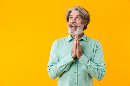 Picture of hopeful emotional elderly grey-haired bearded man in blue shirt posing isolated over yellow wall background showing please pray gesture.