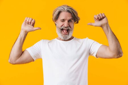 Image of happy senior grey-haired bearded man posing isolated over yellow wall background pointing to himself.