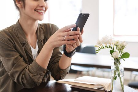 Cropped image of a smiling pretty young woman relaxing at the cafe indoors, using mobile phone Stockfoto