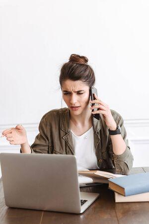 Bild einer schönen jungen verwirrten unzufriedenen Frau, die zuhause Laptop-Computer verwendet und per Handy spricht. Standard-Bild