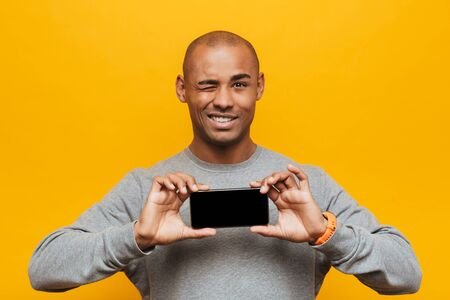 Portrait of an attractive smiling confident casual young african man standing over yellow background, showing blank screen mobile phone