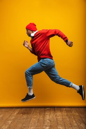 Full length side view portrait of an attractive confident casual young african man running over yellow background