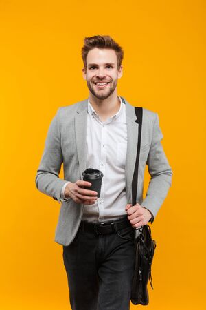 Handsome smiling young businessman wearing jacket standing isolated over yellow background, carrying bag, holding takeaway coffee cup Stock fotó