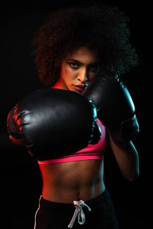 Image of young african american sportswoman working out in boxing gloves isolated over black background