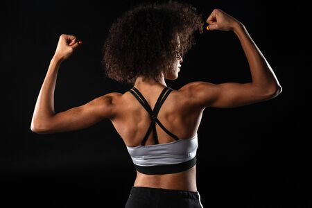 Image from back of african american sportswoman showing her biceps isolated over black background Reklamní fotografie