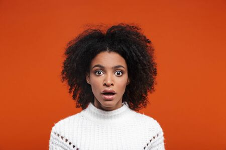 Shocked young attractive african woman looking at camera isolated over red background Stock fotó