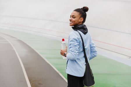 Smiling fit young african sportswoman carrying sportsbag standing at the stadium, holding water bottle