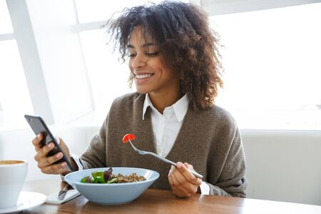 Portrait of young beautiful african american woman using cellphone while having lunch in cafe Stockfoto