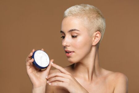 Picture of a beautiful young blonde stylish woman with short haircut posing isolated over dark beige wall background holding cream. Stock fotó