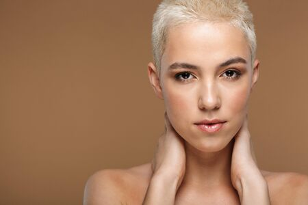Image of a beautiful young blonde stylish woman with short haircut posing isolated over dark beige wall background. Stock fotó