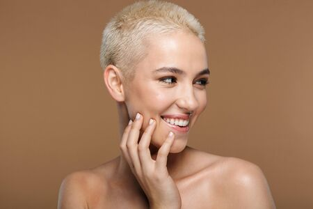 Image of a beautiful happy optimistic smiling young blonde stylish woman with short haircut posing isolated over dark beige wall background. Stock fotó