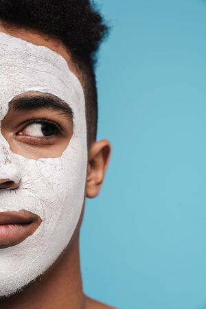 Cropped photo of calm african american man in facial cosmetic mask looking aside isolated over blue background
