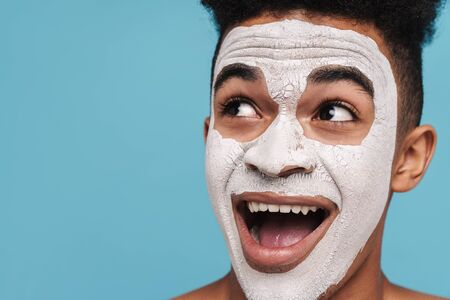 Photo of excited african american man in facial cosmetic mask looking aside isolated over blue background