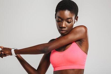 Image of african american sportswoman using wireless earbuds while working out isolated over white background