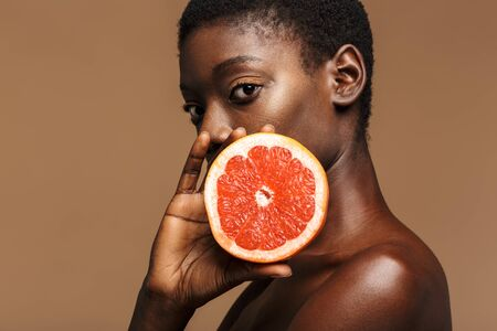 Beauty portrait of pretty young half-naked african woman holding grapefruit part isolated over brown background