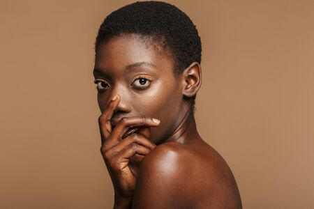 Beauty portrait of attractive young half-naked african woman with short black hair isolated over beige background