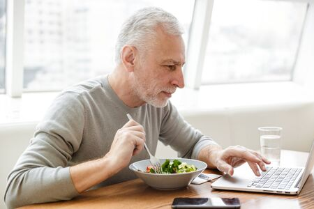 Image of a serious mature senior grey-haired bearded businessman sit in cafe have a dinner using laptop computer.
