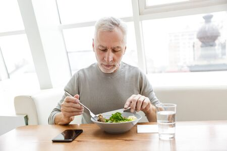 Picture of a mature senior grey-haired bearded businessman sit in cafe have a dinner.