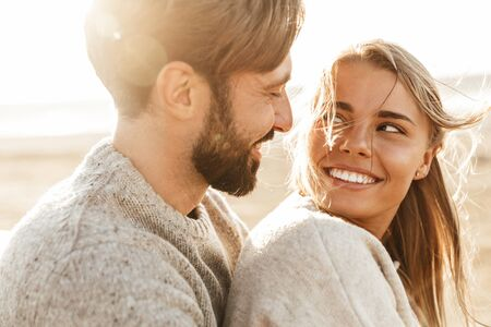 Close up of a smiling beautiful young couple embracing while standing at the beach Stock Photo