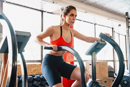Confident young attractive sportswoman exercising on an elliptical machine at the gym