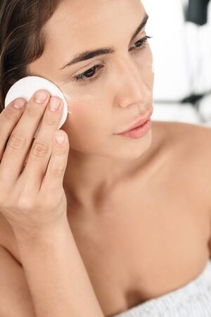 Portrait of adorable young half-naked woman removing makeup with cotton pad isolated over white background