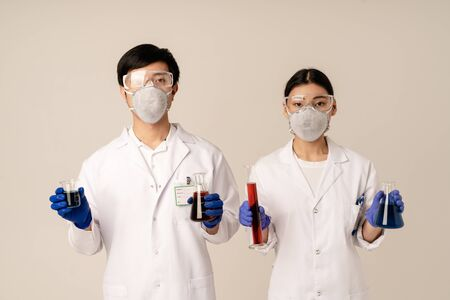 Image of asian young doctors wearing uniform and protective masks holding medical tubes with liquid isolated over beige background