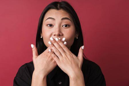Close up of a pretty young asian woman wearing casual clothes standing isolated over red background, cover mouth