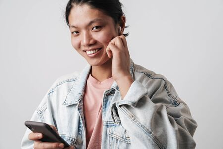 Image of joyful asian man smiling while using cellphone and wireless earphone isolated over white background Banque d'images