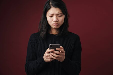 Image of perplexed asian man posing and using cellphone isolated over burgundy background