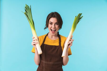 Image of cute happy young woman chef holding leek isolated over blue wall background.