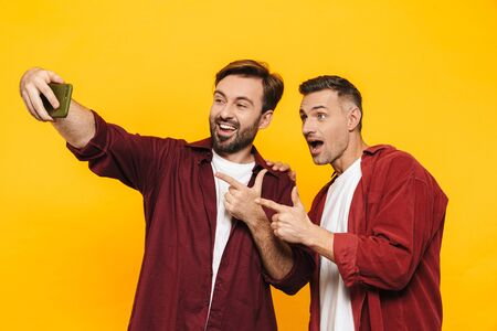 Two attractive cheerful excited young men friends wearing casual clothes standing isolated over yellow background, taking a selfie, pointing fingers