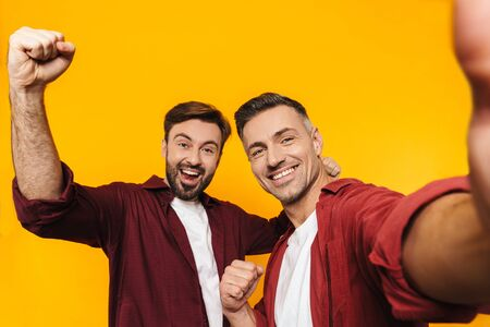 Two attractive cheerful excited young men friends wearing casual clothes standing isolated over yellow background, taking a selfie