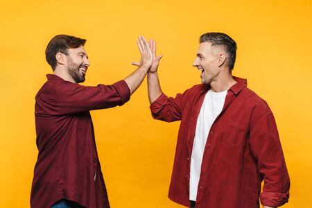 Image of two handsome men 30s in red shirts smiling and giving high five isolated over yellow background