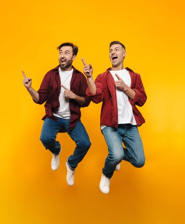 Full length image of two handsome men 30s in red shirts smiling and pointing fingers at copyspace isolated over yellow background