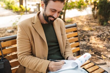 Image of handsome adult man in jacket woking and holding clipboard while sitting on bench in park