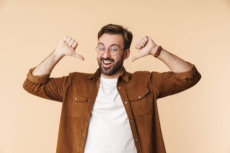 Portrait of a cheerful young arttractive bearded man wearing casual clothes standing isolated over beige background, pointing fingers at himself