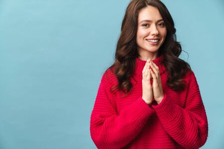 Portrait of an attractive smiling young woman with long brunette hair wearing sweater standing isolated over blue background, asking for something
